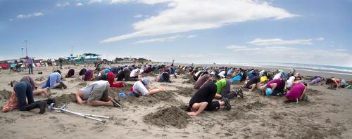 In Christchurch, 220 people put their #HeadsinSandNZ on New Brighton beach. Photo: Alan Bishop