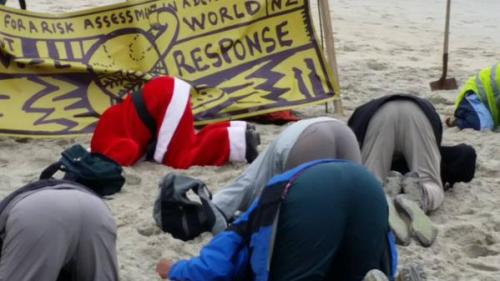 Santa took time out of his schedule to take part in #HeadsInSandNZ in Dunedin yesterday. Photo: Metiria Turei MP